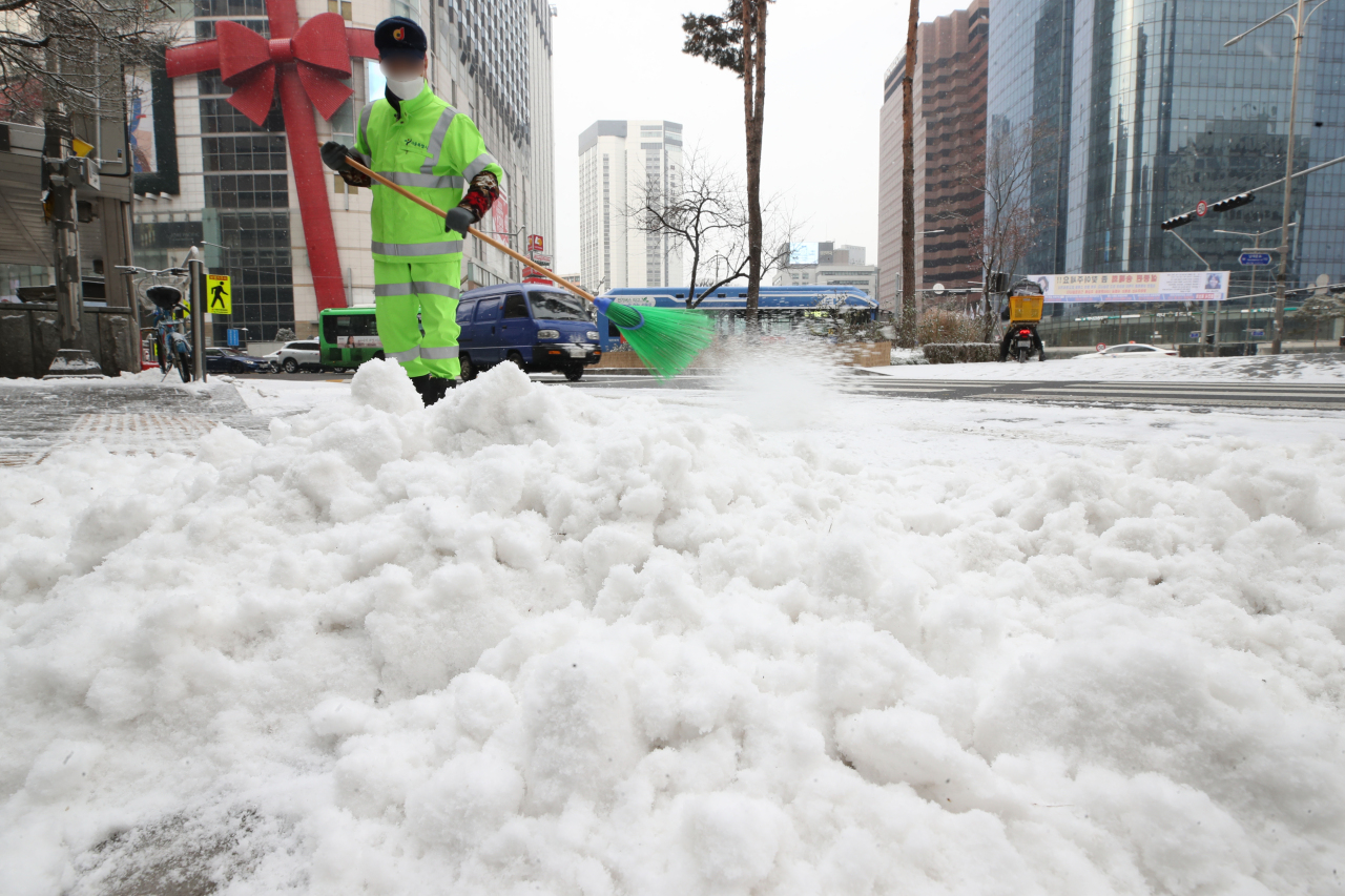 A gongmugwan sweeps the snowy streets of Euljiro, central Seoul on Monday. (Yonhap)