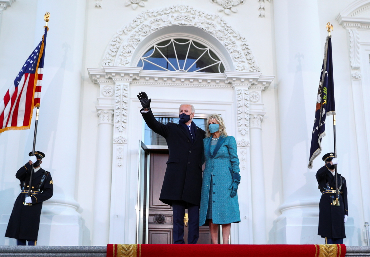 US President Joe Biden waves next to first lady Jill Biden as they stand at the North Portico of the White House, in Washington, US, Wednesday. (Reuters-Yonhap)