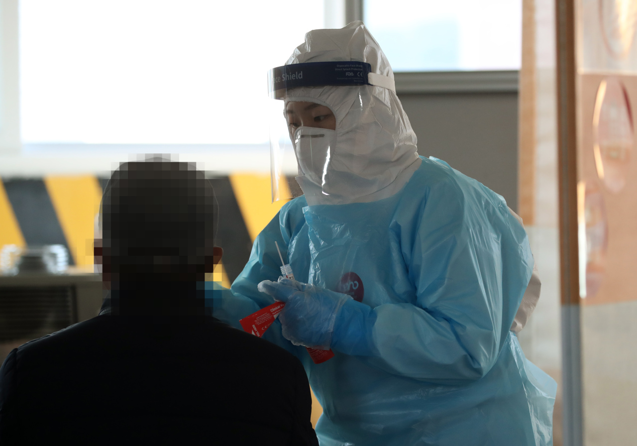 This photo taken on Wednesday, shows a health worker clad in protective suit collecting a sample from a citizen at a makeshift virus testing clinic in the southwestern city of Gwangju. (Yonhap)