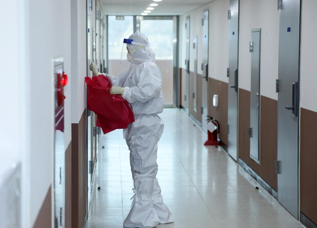 This photo taken on Thursday, shows a health worker clad in a protective suit checking a dormitory at the Joongbu University campus in Goyang, north of Seoul, that is being used as a temporary shelter for arrivals from overseas. (Yonhap)