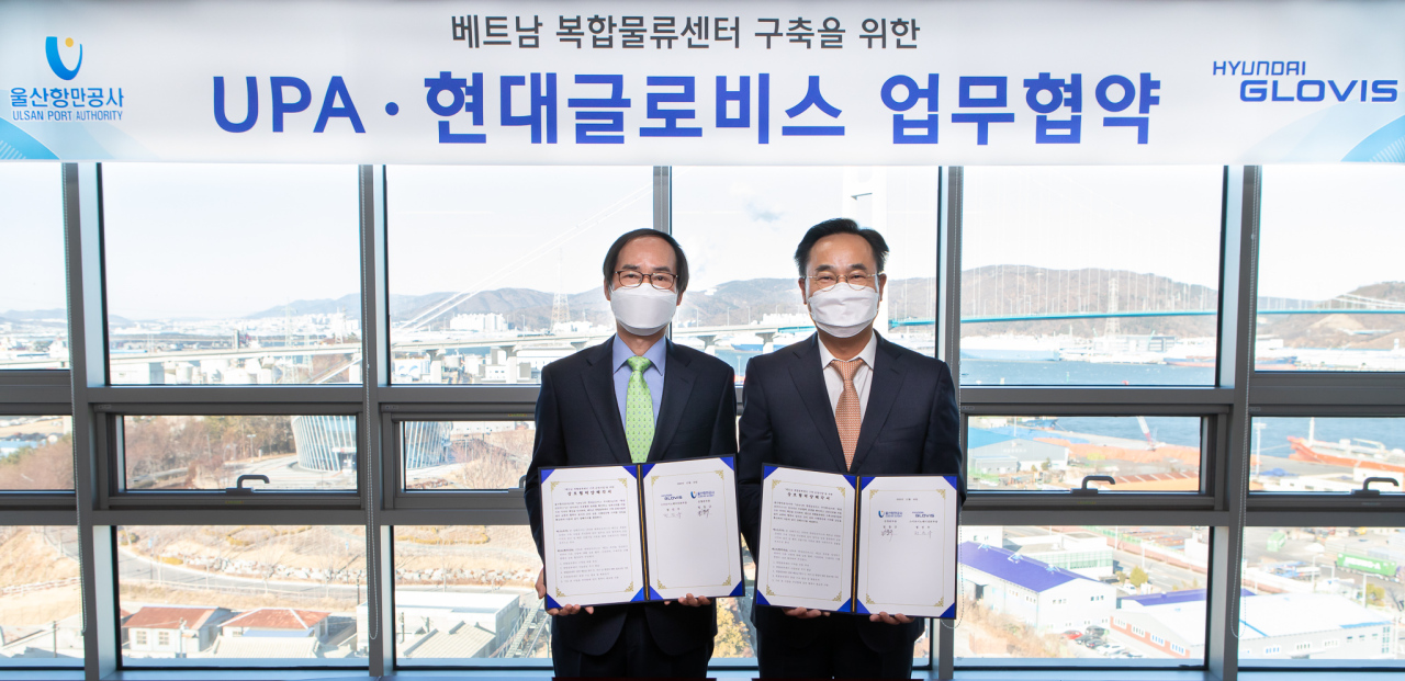 Hyundai Glovis' executive vice president Jung Jin-woo (right) poses with his counterpart from Ulsan Port Authority, Jeong Chang-gyu, at an MOU signing ceremony in Ulsan on Jan. 14. (Hyundai Glovis)