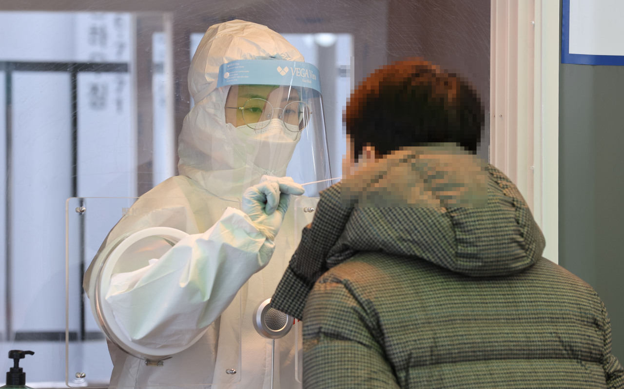 A medical worker collects a swab sample for a coronavirus test at a makeshift COVID-19 screening facility in Seoul on Saturday. (Yonhap)