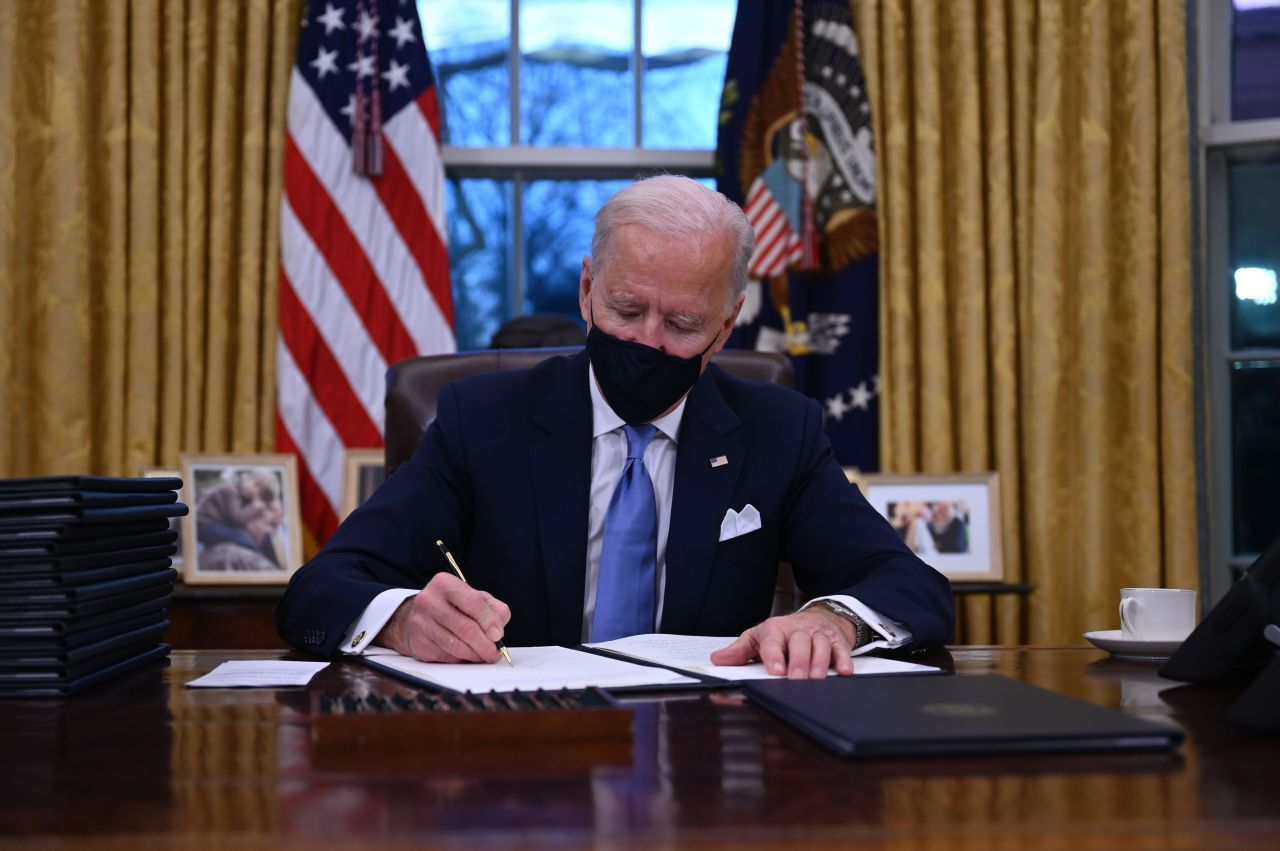 US President Joe Biden sits in the Oval Office as he signs a series of orders at the White House in Washington, after being sworn in at the US Capitol last Wednesday. (AFP-Yonhap)