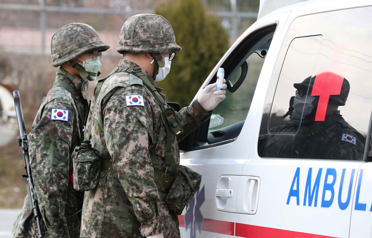 This file photo, taken Feb. 26, 2020, shows service members checking the driver of an ambulance for fever near its base in northern Daegu, 300 kilometers southeast of Seoul. (Yonhap)