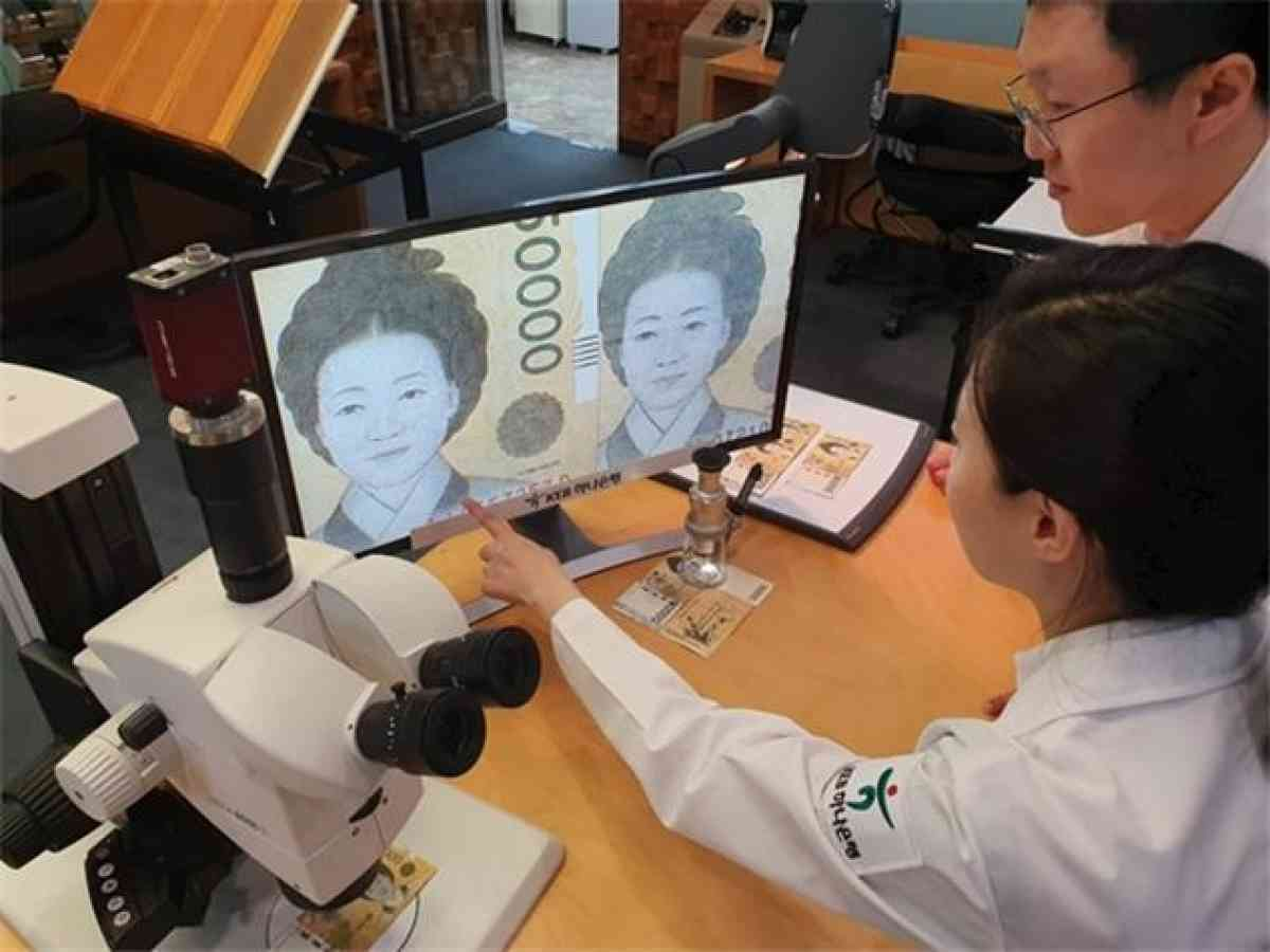 In the photo, provided by KEB Hana Bank, bank officials closely examine a magnified image of what appears to be a fake banknote at a Seoul branch office on Sept. 23, 2019. (KEB Hana Bank)