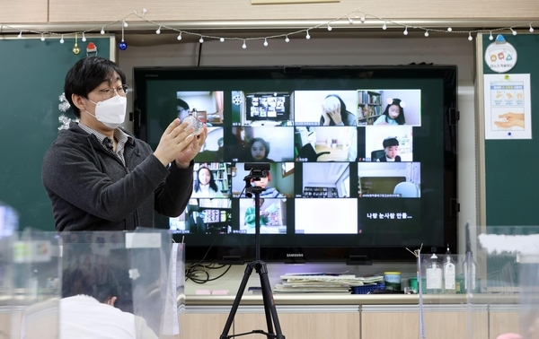 In the Dec. 14, 2020, file photo, a screen behind a teacher shows students taking an online class at Hwarang Elementary School in Seoul on Dec. 14, 2020. (Yonhap)