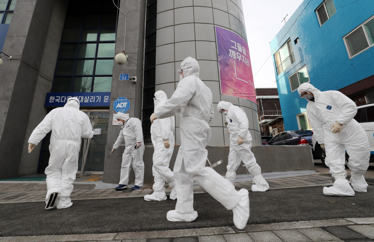Disease officials are work Monday to carry out disinfection and restrict access at the IEM School in Daejeon. (Yonhap)