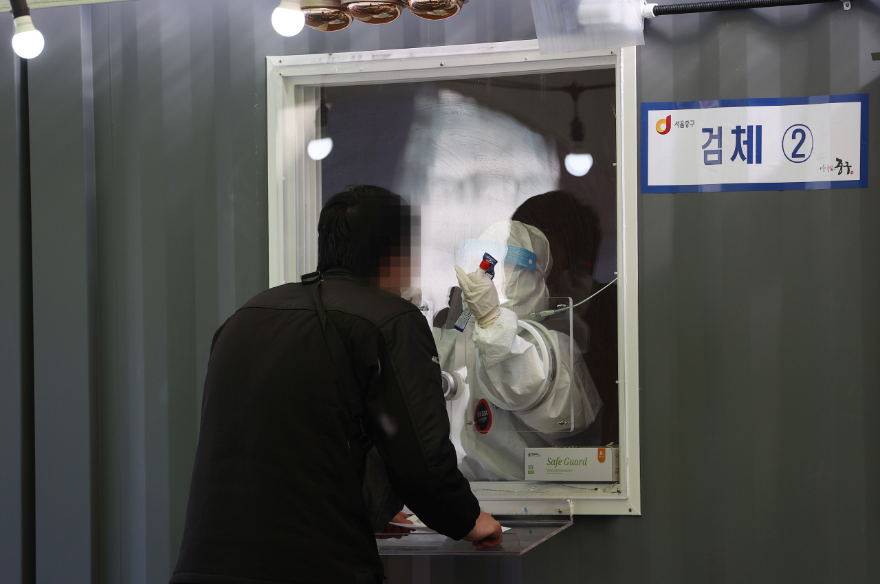 A medical worker collects a specimen for coronavirus testing at a temporary clinic in front of Seoul Station on Sunday. (Yonhap)