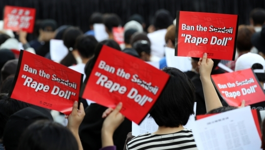 "Demonstraters hold up placards saying ""Rape Doll"" at a rally protesting the import of life-size sex dolls. The rally was held near Cheonggye Stream in central Seoul in September 2019. (Yonhap)"