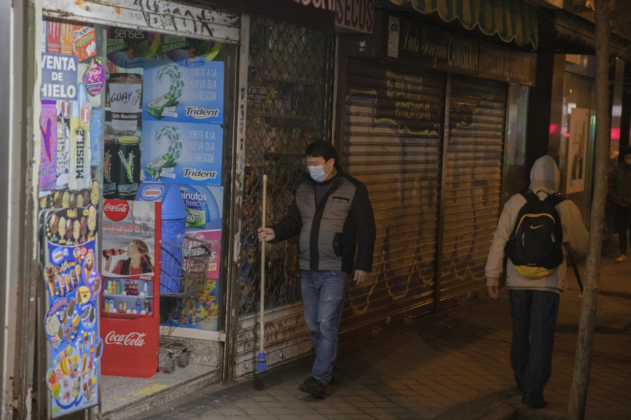 A shop worker prepares to close before the new 10 p.m. curfew comes into effect to control the coronavirus pandemic, in Madrid on Monday. (AP-Yonhap)