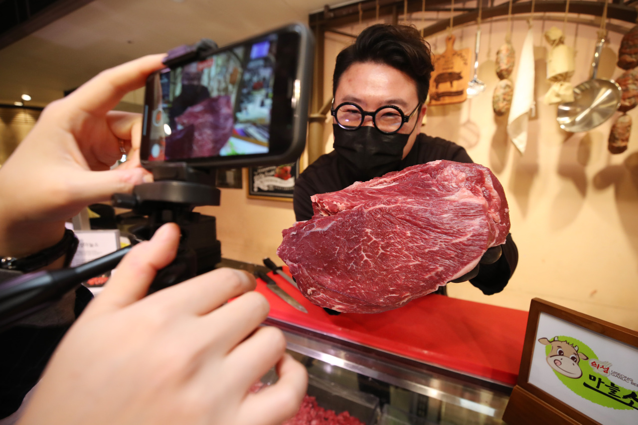 A butcher at the Lotte Department Store in Daegu displays meat during a live commerce show while chatting to viewers on Dec. 29, 2020. (Yonhap)