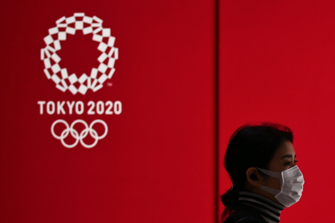 A woman in a face mask walks past a display showing the Tokyo 2020 Olympic Games logo in Tokyo on March 24, 2020. (AFP-Yonhap)