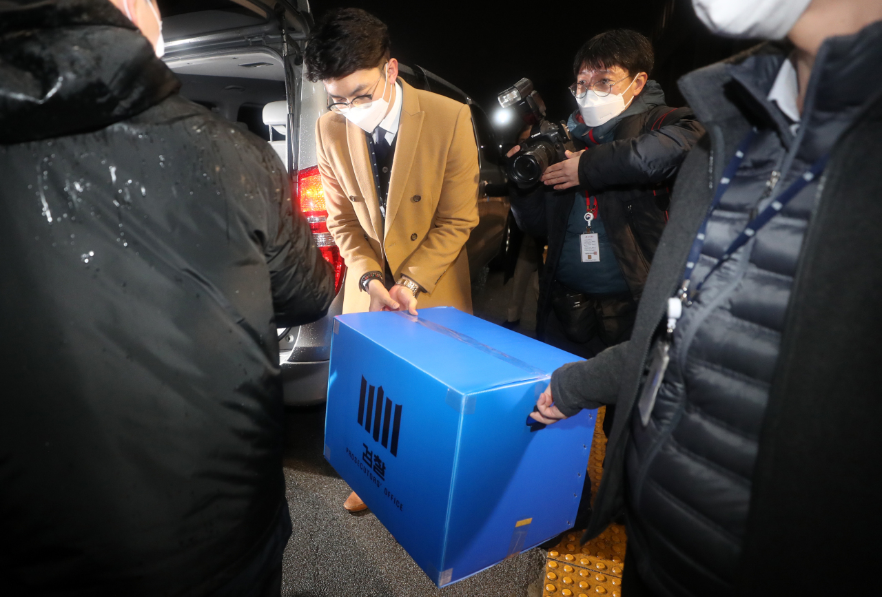 Investigators carry a box of documents out of the Ministry of Justice after making a raid into the ministry in connection with an investigation into an allegedly illegal overseas travel ban on Kim Hak-ui, a former vice justice minister, in Gwacheon, south of Seoul, last Thursday. (Yonhap)