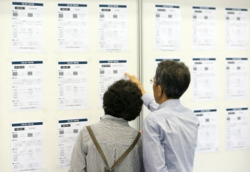 This file photo, taken Sept. 19, 2018, shows senior jobseekers looking at postings at a job fair in the southeastern port city of Busan. (Yonhap)