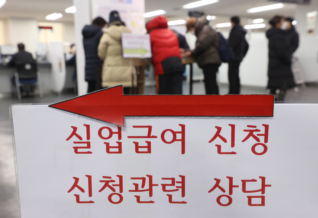 A group of people fill out applications for unemployment benefits at a regional office of the Employment and Welfare Plus Center in Seoul earlier this month. (Yonhap)