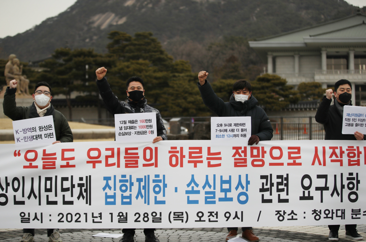 Leaders of small business groups hold a press conference outside Cheong Wa Dae in Seoul on Thursday, demanding the easing of social distancing restrictions and compensation for their losses. (Yonhap)