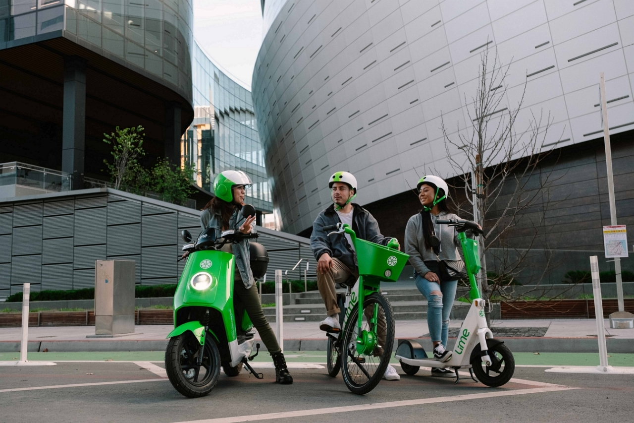 Models pose with (left to right) an electric moped, an electric bicycle and an electric scooter from Lime. (Lime)
