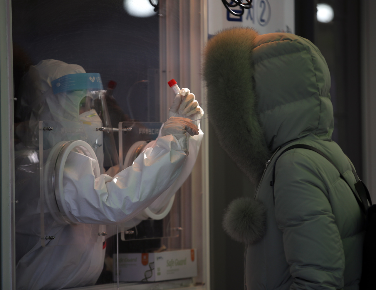 A medical worker takes nose swabs of a citizen at a walk-in testing booth near Seoul Station on Friday. (Yonhap)