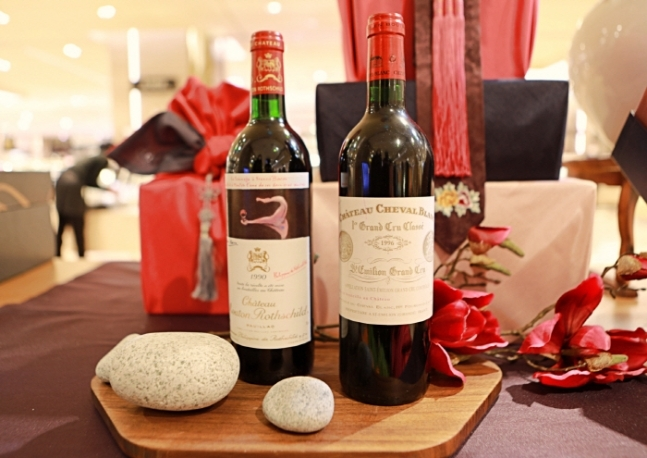 Bottles of Chateau Mouton Rothschild 1990 (left) and Chateau Cheval Blanc 1996 are displayed at Lotte Department Store as Seollal gifts. (Lotte Department Store)