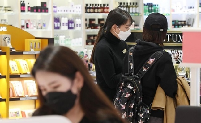 Staff and shoppers look at products at a cosmetics store. (Yonhap)