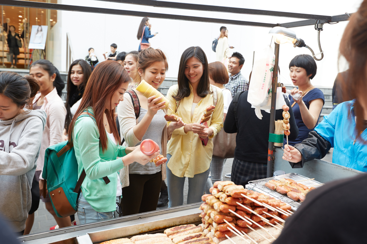 Tourists from abroad try food at a street stall in Seoul. (Korea Tourism Organization)