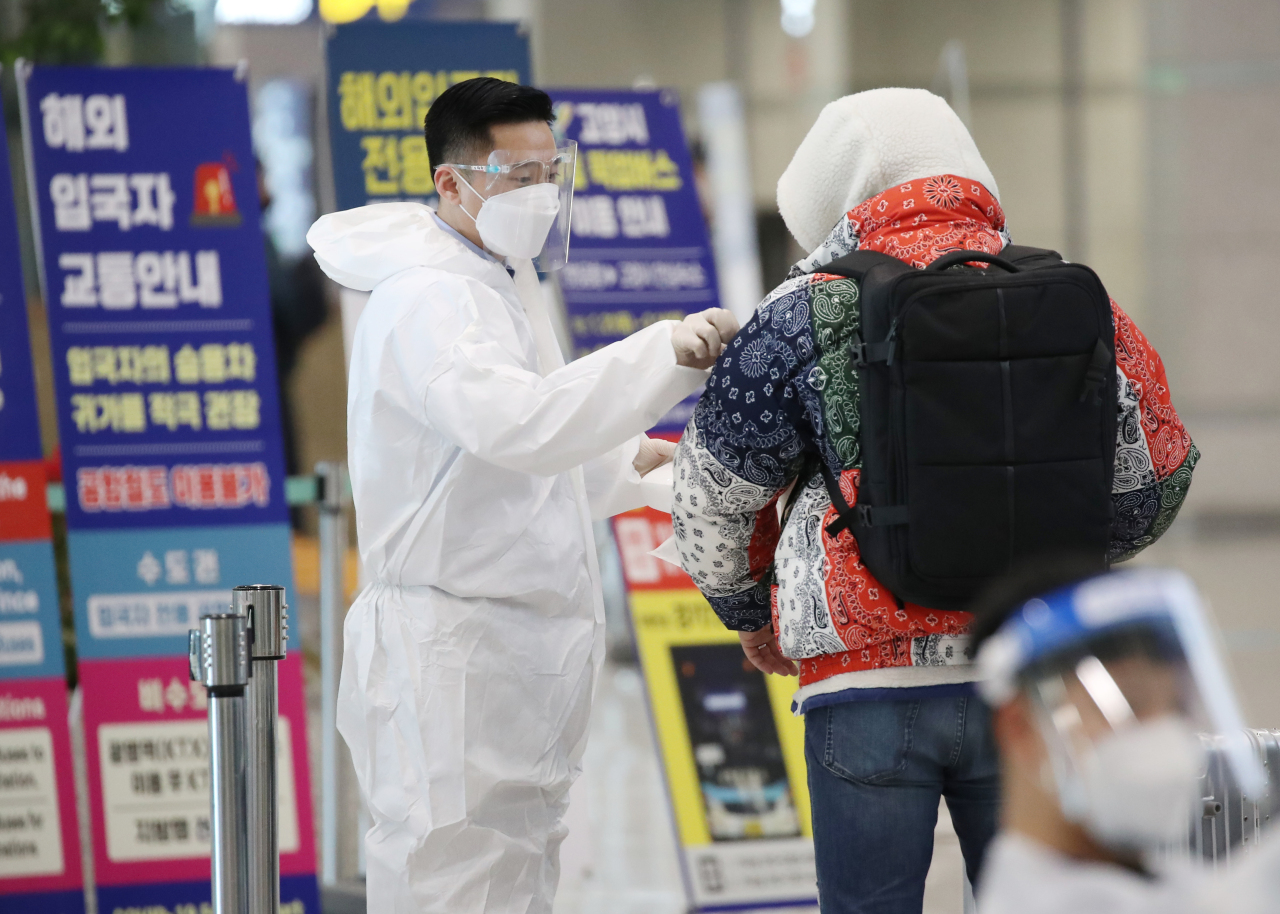 A quarantine official attaches a sticker to the shoulder of a passenger from abroad at Incheon airport, west of Seoul, on Monday. (Yonhap)