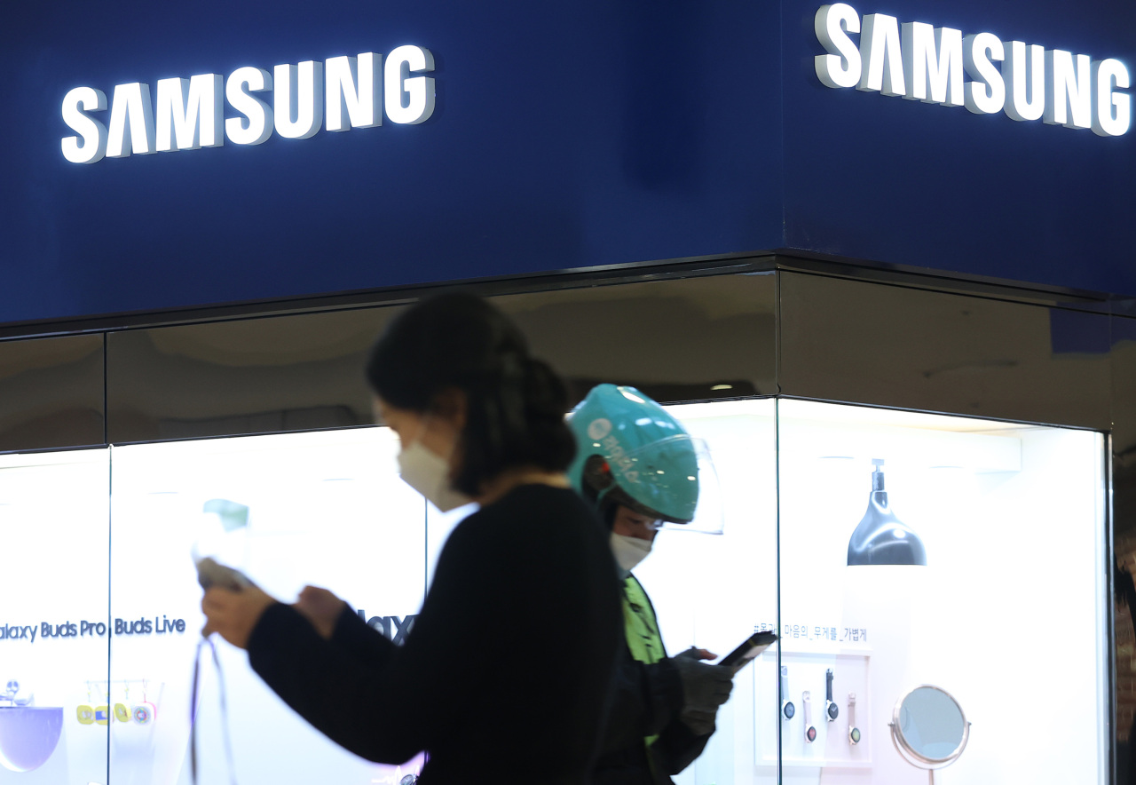 his file photo taken on Jan. 28, 2021, shows citizens with smartphones at Samsung Electronics Co.'s office building in Seoul. (Yonhap)