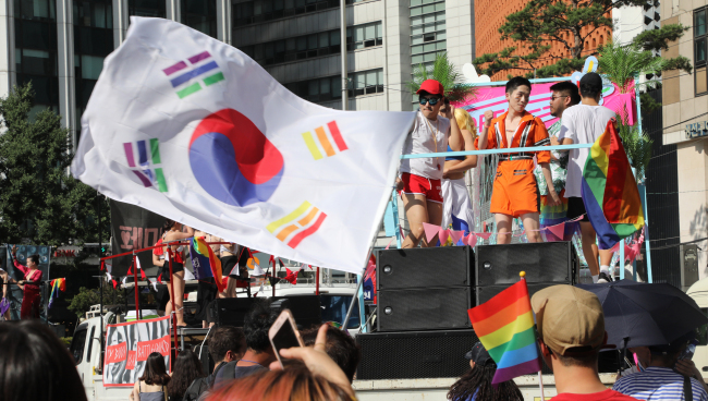 Participants march through central Seoul at the Pride Parade in central Seoul on July 14, 2018, waving a rainbow-colored South Korean national flag, among others. (Yonhap)