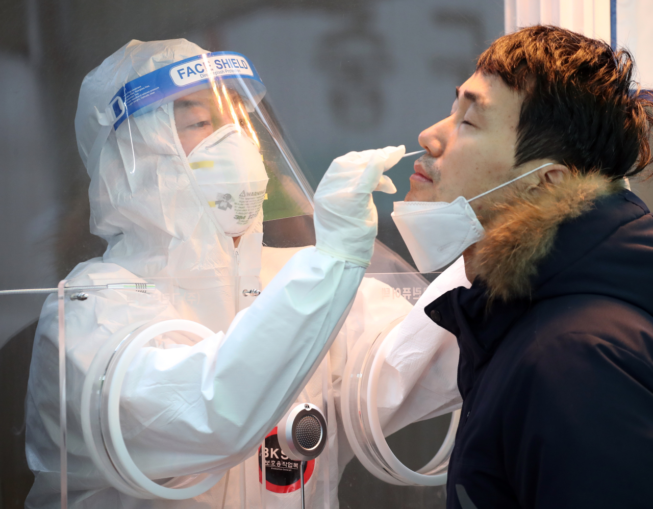 Ahn Cheol-soo, head of the minor opposition People's Party, carries out a new coronavirus test on a visitor at a makeshift COVID-19 clinic in front of Seoul Station, Thursday. (Yonhap)
