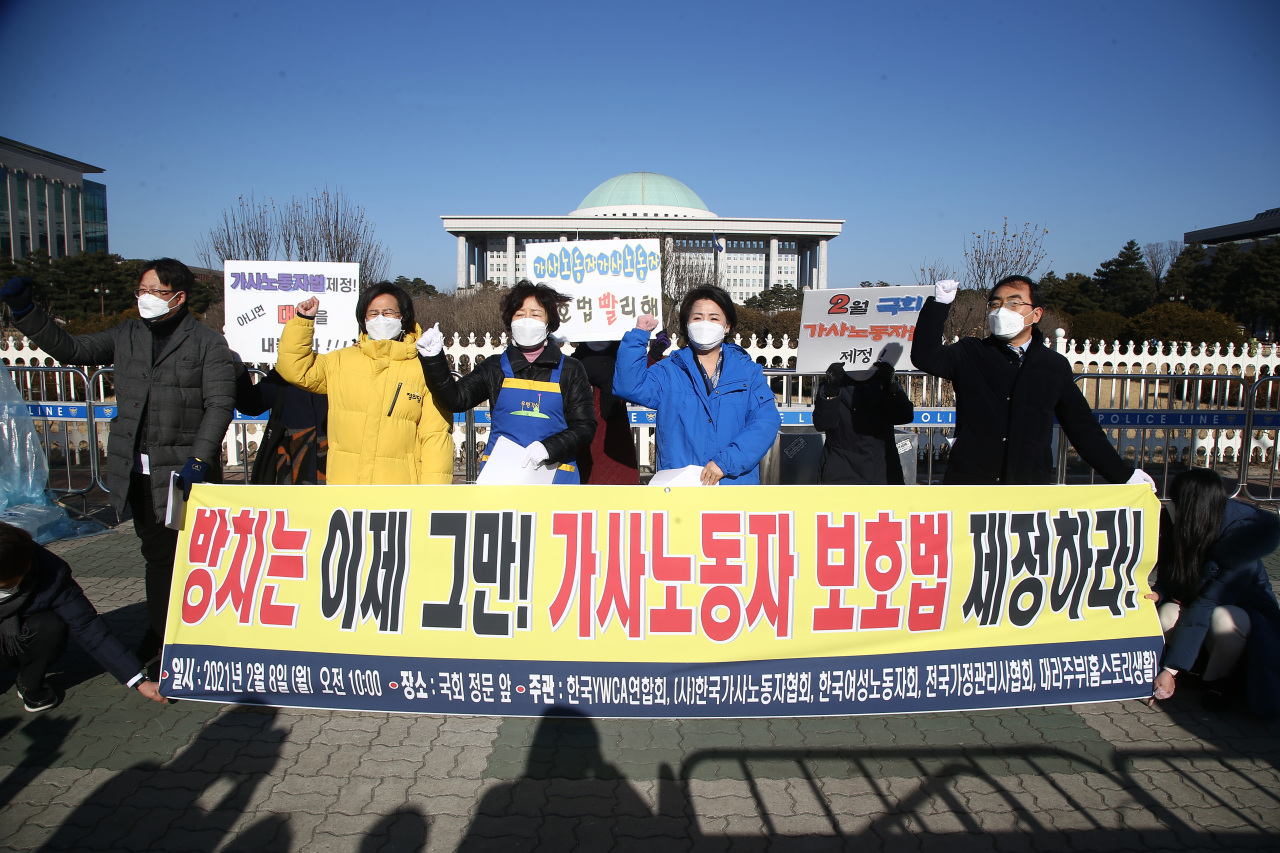 Rep. Kang Eun-mi of the progressive minior Justice Party (second from left) and Rep. Lee Soo-jin of the Democratic Party of Korea (center right) call for improved working conditions for domestic workers during a press conference held earlier this month in front of the National Assembly in Yeouido, western Seoul. (Yonhap)