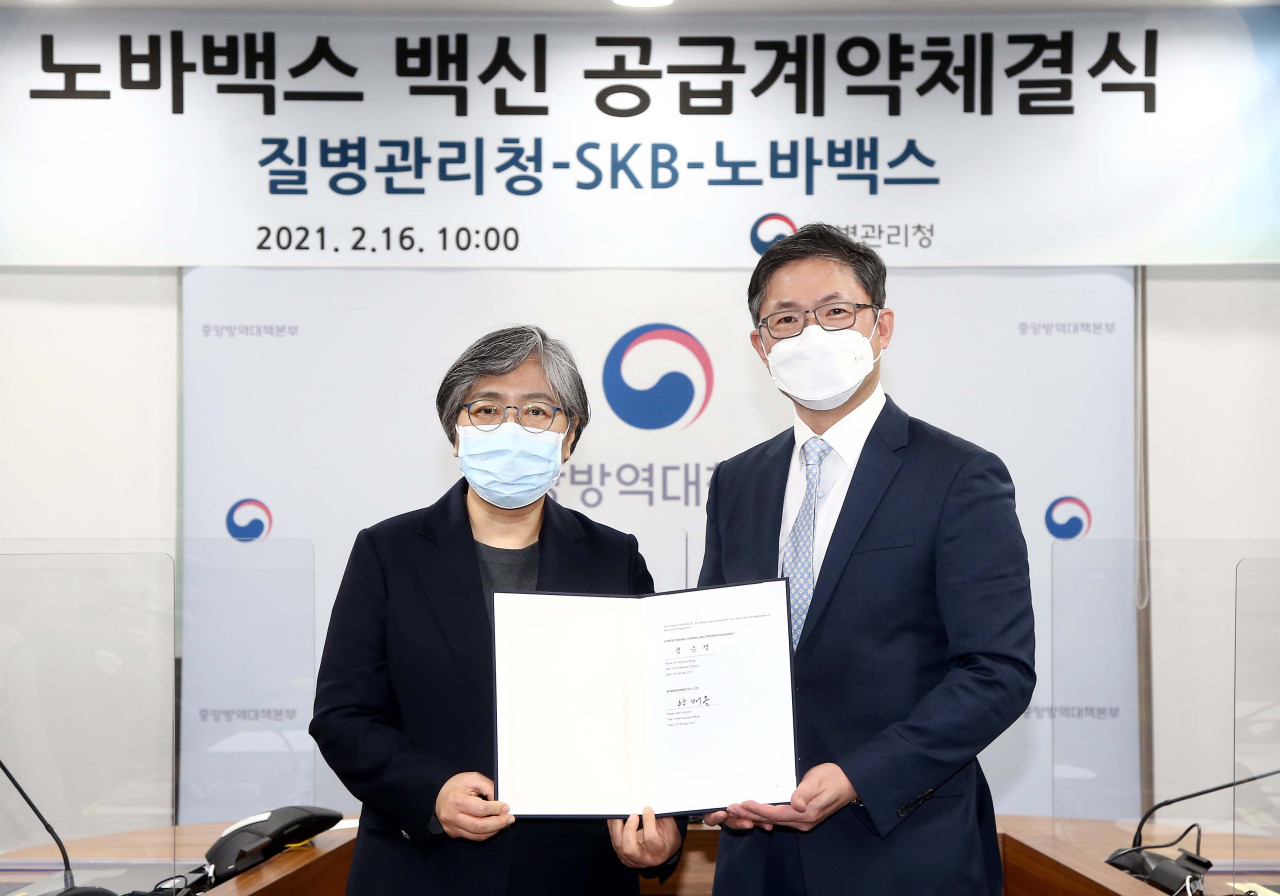 Korea Disease Control and Prevention Agency Commissioner Jeong Eun-kyeong (left) and SK Bioscience CEO Ahn Jae-yong sign a deal to supply Novavax vaccines to the Korean population on Feb. 16. (SK Bioscience)