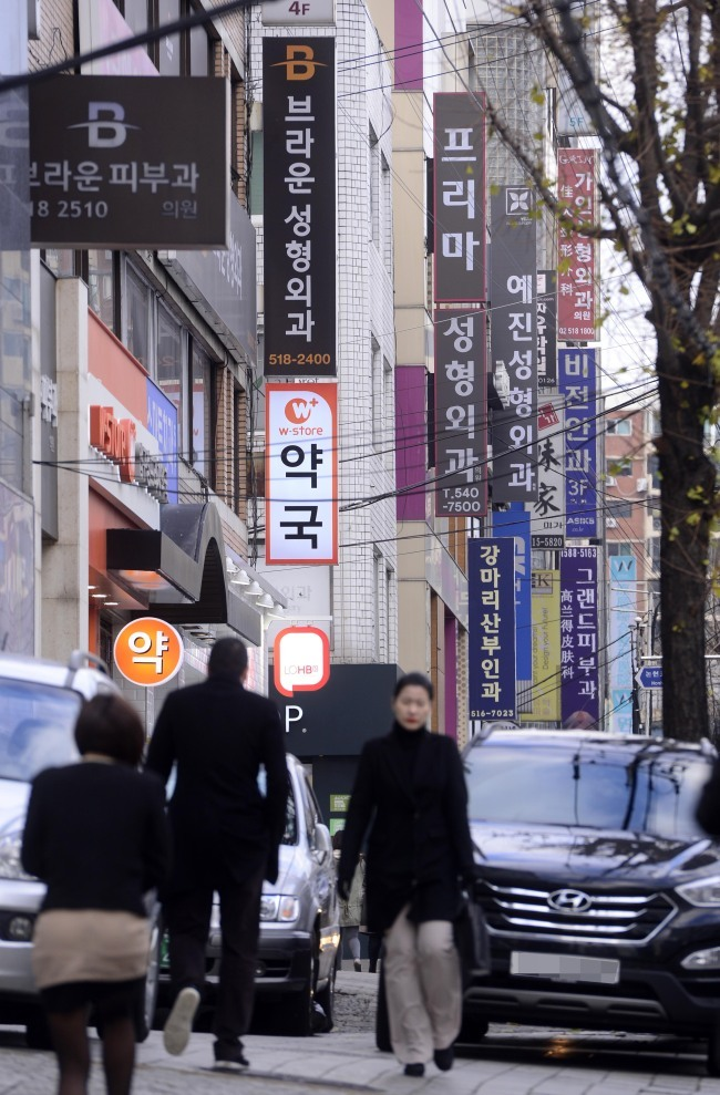 People walk down a street lined with cosmetic surgery clinics in Apgujeong-dong in Seoul in 2013. (Park Hae-mook/The Korea Herald)