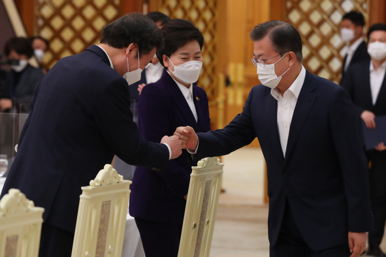 President Moon Jae-in (R) bumps fists with ruling Democratic Party leader Lee Nak-yon during a meeting at Cheong Wa Dae in Seoul on Friday. (Yonhap)