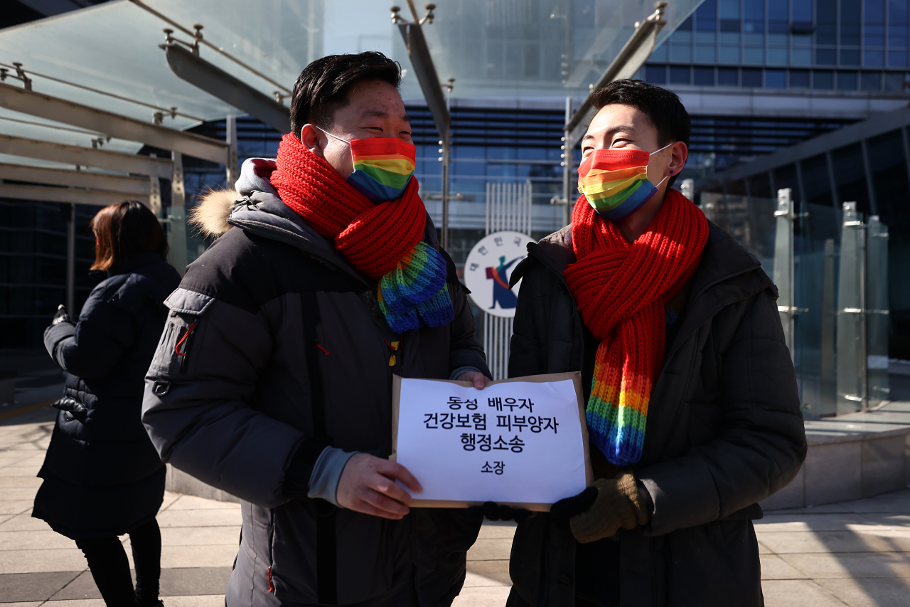 So Seong-wook (L) and Kim Yong-min, a South Korean gay couple, stand in front of the Seoul Administrative Court in southern Seoul on Friday, before filing an administrative lawsuit against the National Health Insurance Service. (Yonhap)