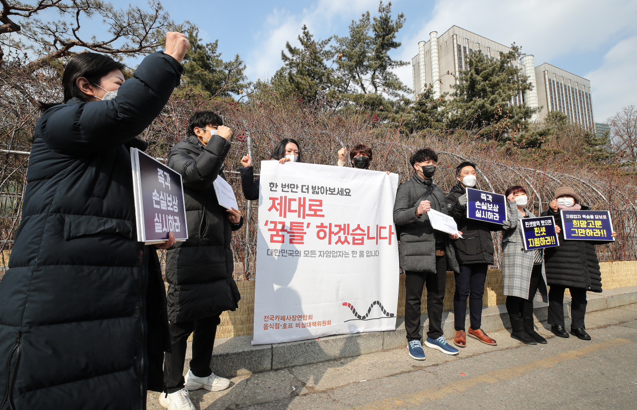 Owners of cafes and restaurants hold a press conference at outside the Seoul Central District Court in southern Seoul on Friday, before filing a compensation suit against the government. (Yonhap)