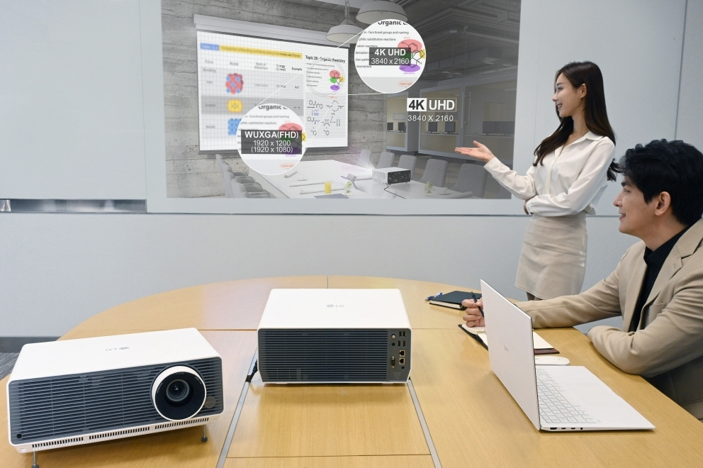 This photo, provided by LG Electronics Inc. on Monday, shows models introducing the company's new LG ProBeam laser projectors for office-use. (LG Electronics Inc.)