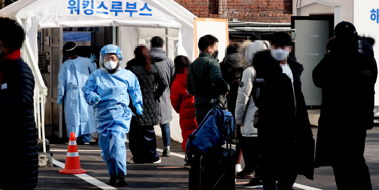 Visitors wait to get tested for the new coronavirus at a makeshift clinic in Seoul on Sunday. (Yonhap)