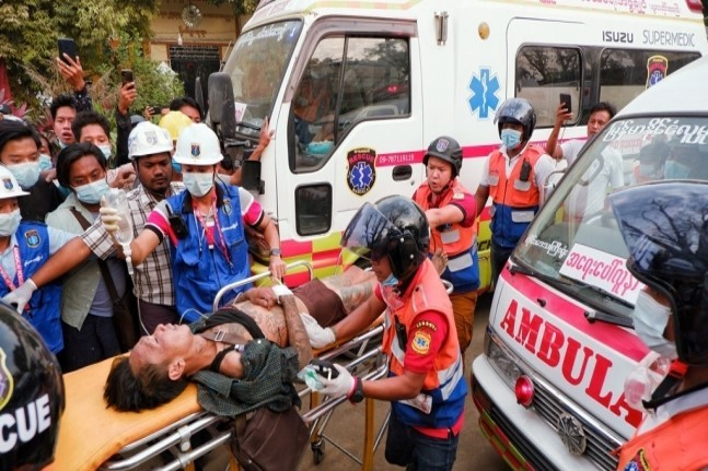 A Myanmar citizen who protested against the military coup gets transported by paramedics on Feb. 20. (Yonhap)