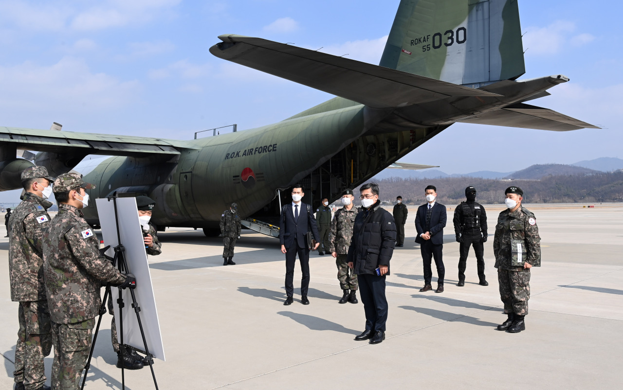 Defense Minister Suh Wook (front) is briefed on the military drill conducted to ship the first batch of coronavirus vaccines with an Air Force transporter plane at Seoul Air Base, Feb. 19, 2021. (Yonhap)
