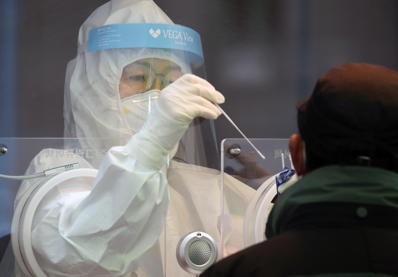 A health care worker at a Seoul testing center performs a nasopharyngeal swab on a patient on Sunday. (Yonhap)