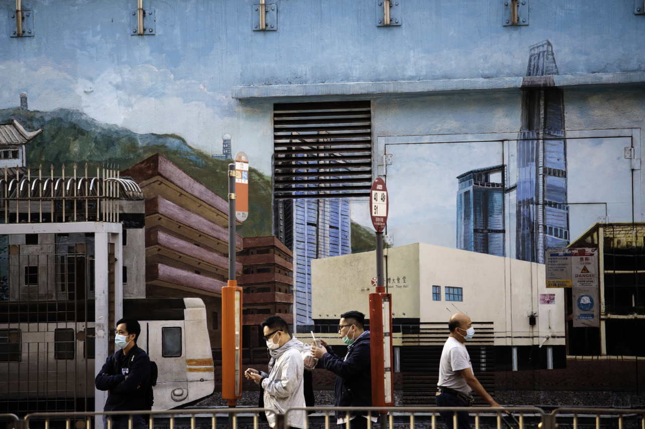 In this Penta Press file photo, passengers wait for bus against a mural of Hong Kong city. (Yonhap)