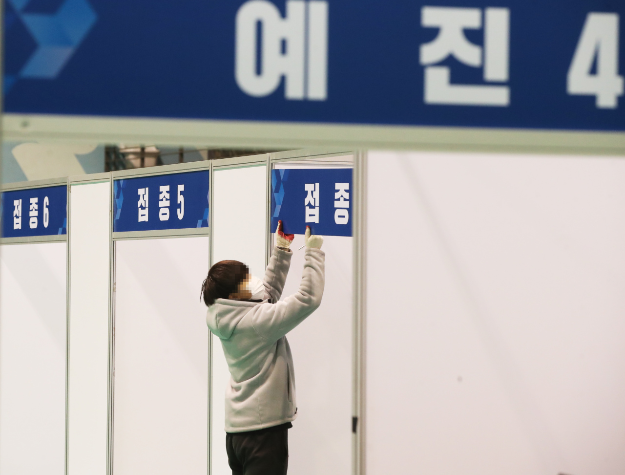 A worker puts up signs at a makeshift COVID-19 vaccination center in Suwon, 46 km south of Seoul, on Monday. (Yonhap)