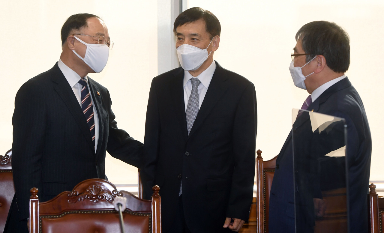 Finance Minister Hong Nam-ki (L) and Bank of Korea Gov. Lee Ju-yeol (C) talk at a meeting on macroeconomic and financial issues in Seoul last Thursday. (Yonhap)