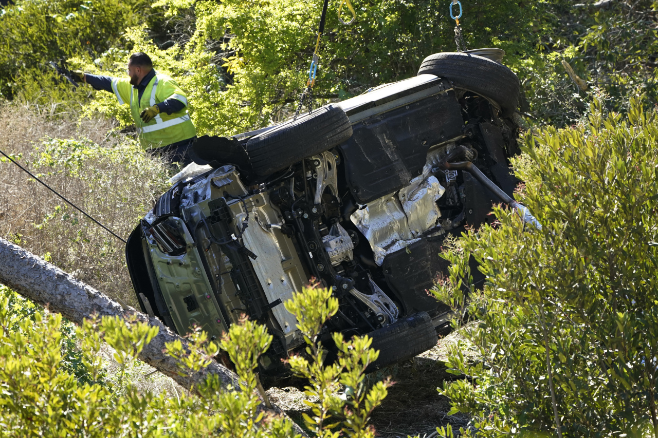 Workers move a vehicle on its side after a rollover accident involving golfer Tiger Woods Tuesday, in Rancho Palos Verdes, Calif., a suburb of Los Angeles. Woods suffered leg injuries in the one-car accident and was undergoing surgery, authorities and his manager said. (AP-Yonhap)