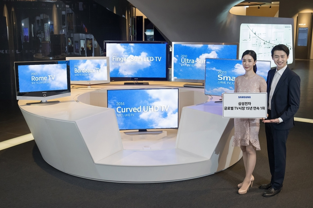 This photo provided by Samsung Electronics Co. on Wednesday, shows models introducing the company's TV products. (Samsung Electronics Co.)