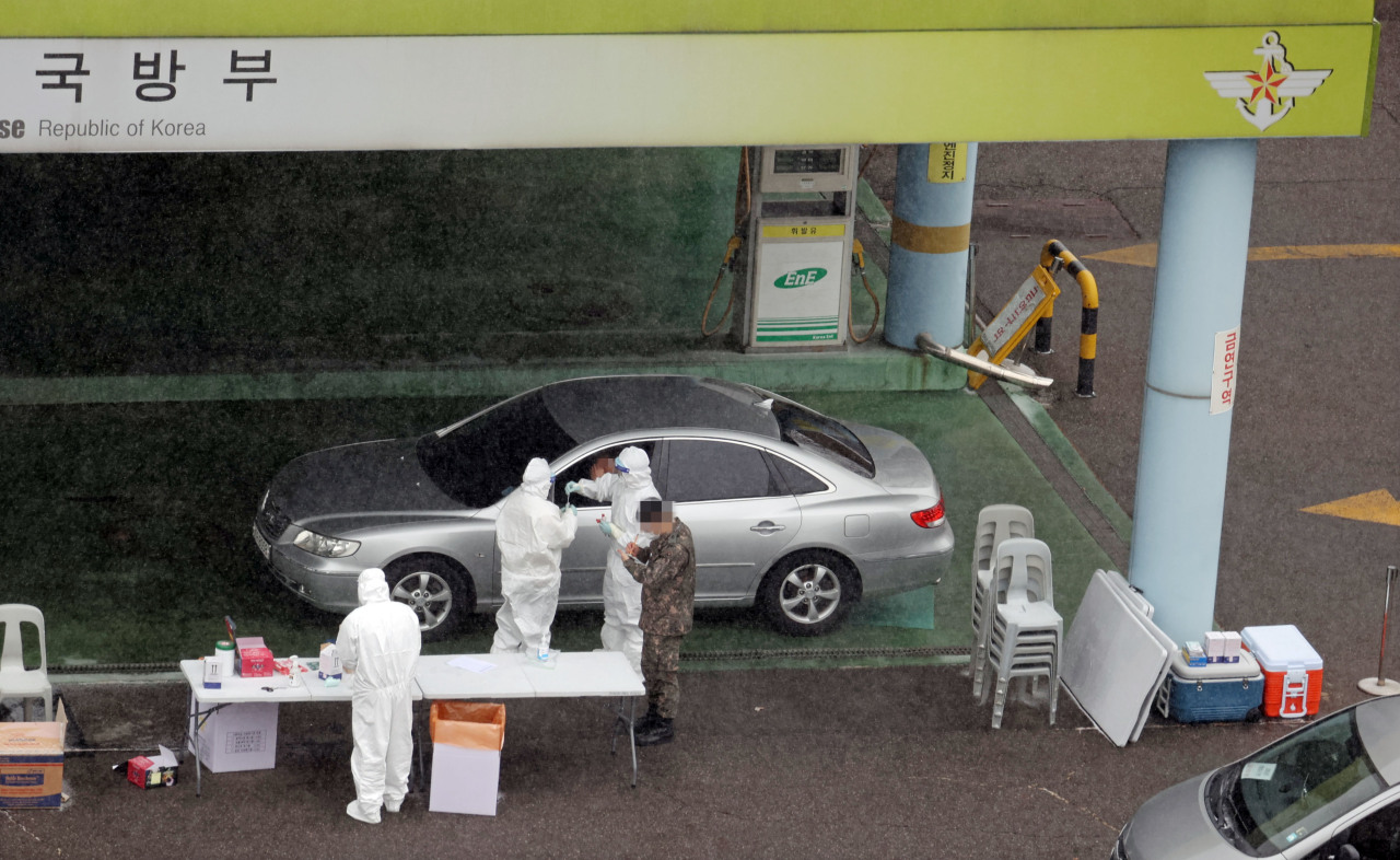 COVID-19 tests are conducted at a drive-thru testing station at the defense ministry in Seoul on Feb. 16, 2021, as the first case among the Joint Chiefs of Staff was reported earlier in the day. (Yonhap)