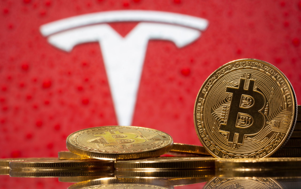 Representations of virtual currency Bitcoin are seen in front of Tesla logo in this illustration taken, February 9, 2021. (Reuters-Yonhap)