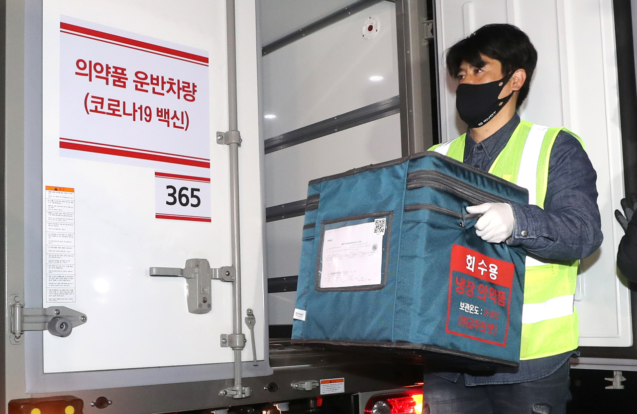 A worker carries a box containing COVID-19 vaccines on the southern resort island of Jeju on Thursday. (Yonhap)