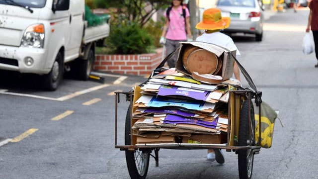 A senior citizen drags a handcart full of cardboard through the streets of Seoul. (Yonhap)