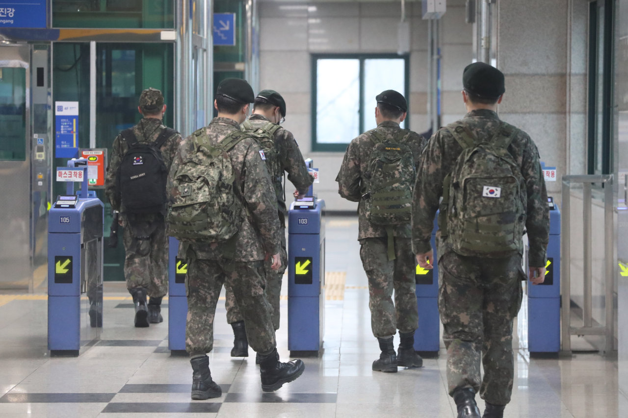 Soldiers enter Munsan Station in Paju, north of Seoul, on Feb. 15, 2021, as the defense ministry lifted a monthslong restriction on military leave the same day in accordance with the easing of the government's social distancing rules against COVID-19. (Yonhap)